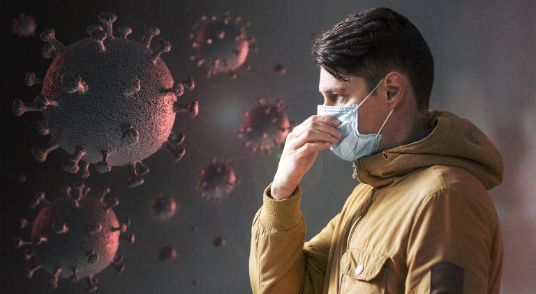 איש עם מסיכה נגד קורונה עומד ומחזיק את האץ מול חיידקים אדומים של וירוס הקורונה