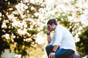 איש יושב ומחזיק את הראש מכאב לפני רקע של עצים ירוקים ומורינגה