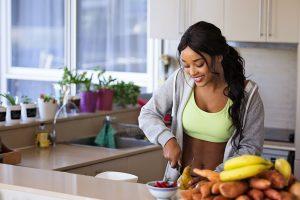 אישה ספורטיבית עם אורח חיים בריא חותכת אגס על השיש ומחייכת